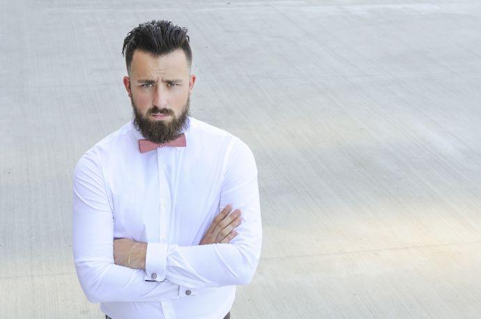 Mann im weißem Hemd trägt Buteo Holzfliege