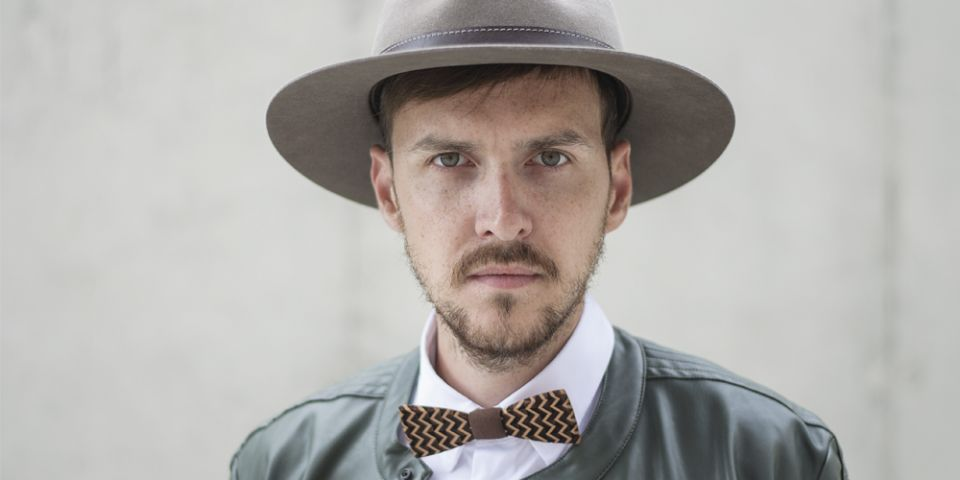 BeWooden - A man wearing brown hat with wooden detail, leather jacket and wooden bow tie.