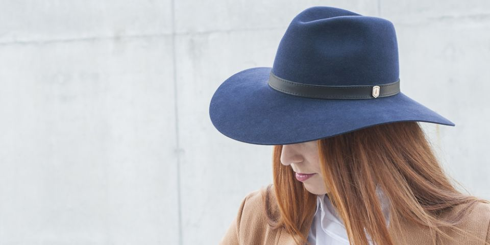 BeWooden - A woman with red hair wearing dark blue hat, brown coat and white shirt.