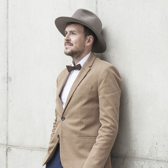 A man wearing the brown Apis hat and a brown jacket