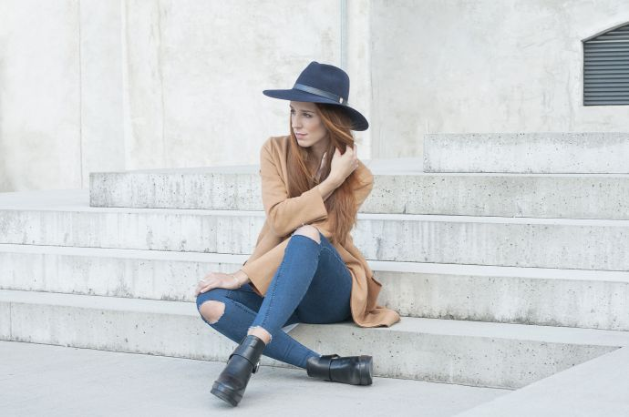 A woman wearing the blue Stellia hat, jeans and a brown coat