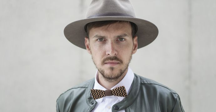 A man wearing the brown Apis hat, a leather jacket and the Decorum wooden bow tie