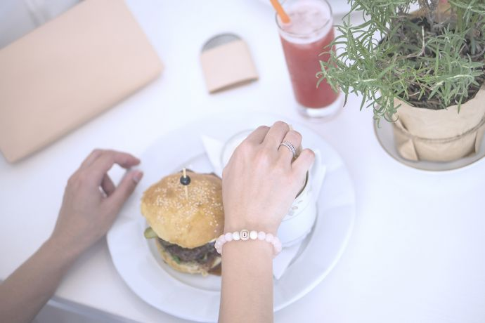 Lunch in a restaurant, on the table lie the leather lady Lux clutch bag and the wooden Liti mirror