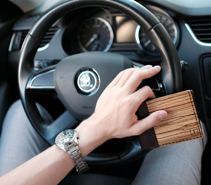 A man behind the wheel with the Nox Virilia wooden wallet