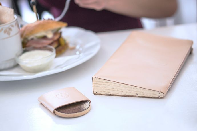 The leather Lux Clutch bag and wooden mirror Liti laid in a restaurant on the table