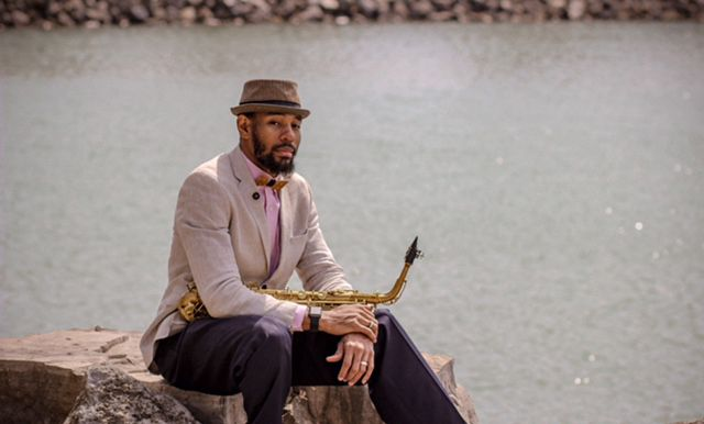 The musician Saxappeal sitting on a stone wearing a hat and the Bellis bow tie holding a saxophone in his hand
