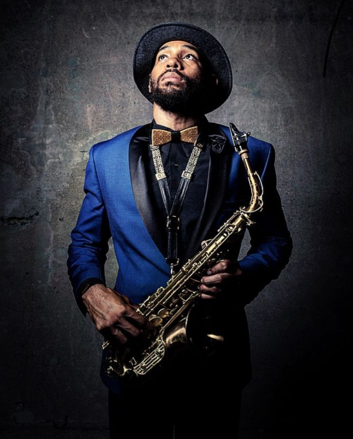 The musician Saxappeal in a blue jacket with a hat and the Bellis wooden bow tie holding a saxophone in his hand