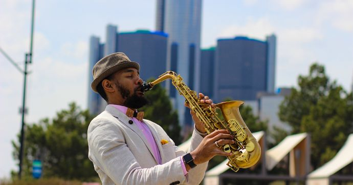 The musician Saxappeal playing saxophone wearing a hat and the Bellis wooden bow tie