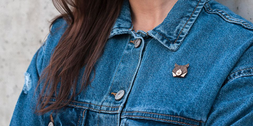A woman in jeans jacket with the wooden brooch Lynx Brooch