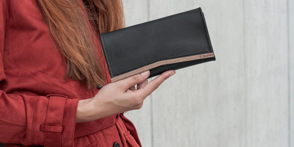 BeWooden - A woman with red hair in an orange coat holding a wallet made of wood and leather Caleo Woman Wallet