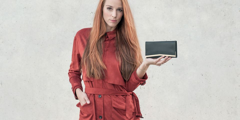 A woman with red hair in an orange coat holding a wallet made of wood and leather Liti Woman Wallet