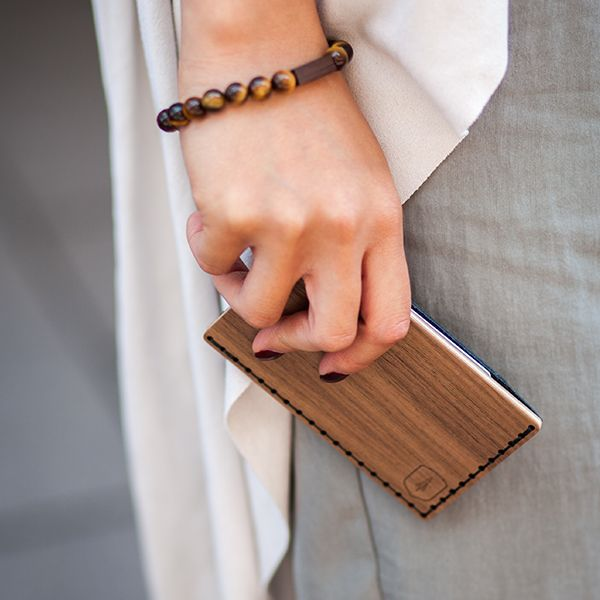 A woman with the wooden cardholder Nox Note in hand