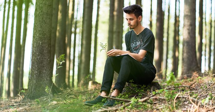 A man sits in a forest and writes in his BeWooden notebook