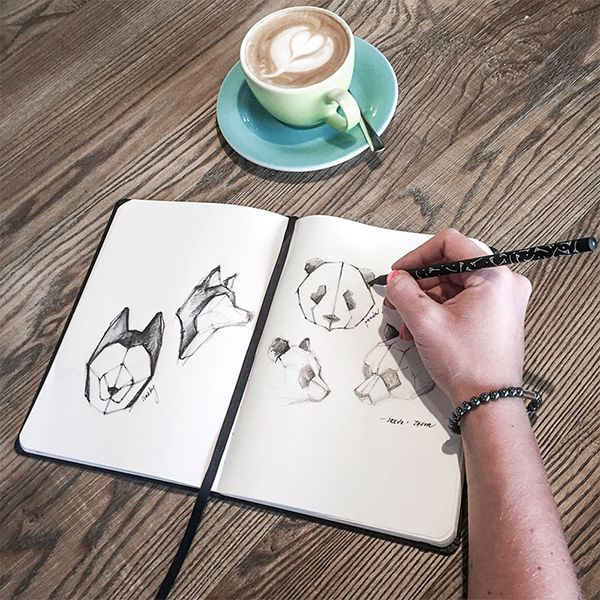 A woman in a café writes in the BeWooden notebook