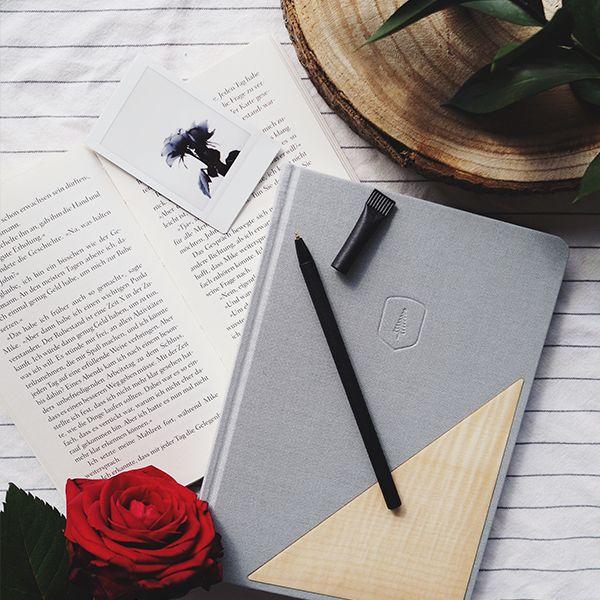 A notebook lies next to a book