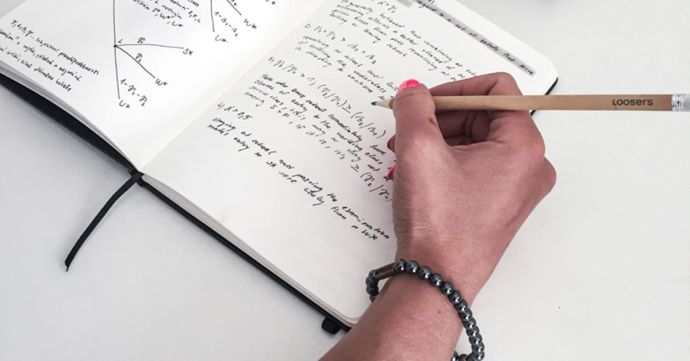 A woman wearing the Silver Hematit bracelet writes in the notebook